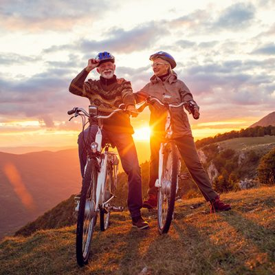 Active seniors having walk with bike in autumn nature. They having romantic time outdoor